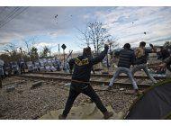 migrantes se enfrentan a la policia de macedonia