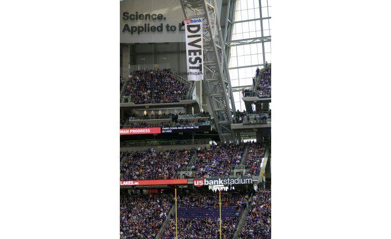 Manifestantes cuelgan pancarta durante juego de Vikings