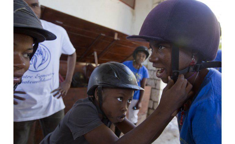 AP Fotos: Montar a caballo ayuda a niño incapacitado