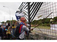 manifestantes derriban la cerca de base aerea en venezuela