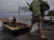 pescan en medio de manchas de petroleo en el lago maracaibo