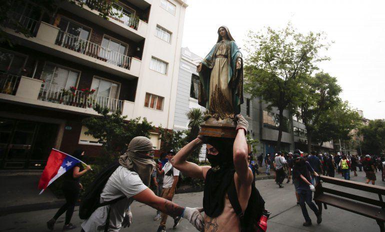 Chilenos enfurecidos arman barricada con estatuas religiosas