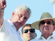 El gobernante cubano Miguel Díaz-Canel y su antecesor, Raúl Castro, custodiados por el nieto de Castro al fondo. (AP)