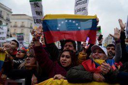 """Archivo: Los venezolanos que viven en España tienen carteles que dicen """"¡Democracia ahora!"""" y banderas venezolanas durante una manifestación en apoyo de la oposición venezolana en Madrid el 25 de enero de 2020. (Foto de JAVIER SORIANO / AFP"""